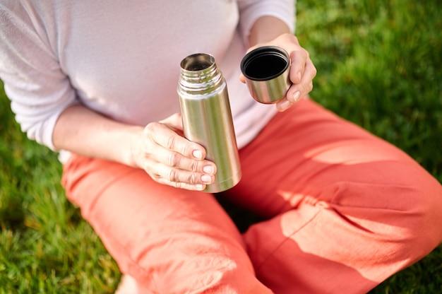 Czas dla siebie. kobiece ręce trzymając otwarty mały termos z napojem na zewnątrz w słoneczny dzień, bez twarzy