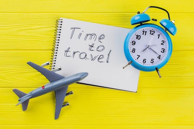 Czas do koncepcji podróży. zabawkowy samolot z budzikiem i notatnikiem.