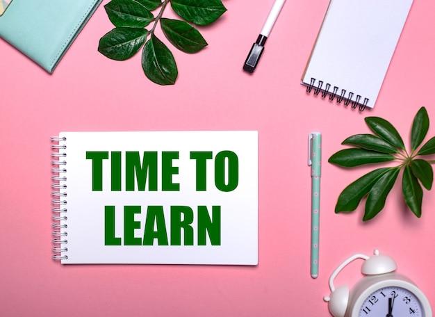 Czas do nauki jest napisany kolorem zielonym na białym notesie na różowej ścianie otoczonej notesami, długopisami, białym budzikiem i zielonymi listkami. koncepcja edukacyjna