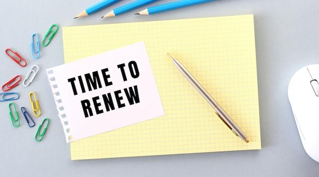 Czas do odnowienia jest zapisany na kartce papieru leżącej na zeszycie obok materiałów biurowych