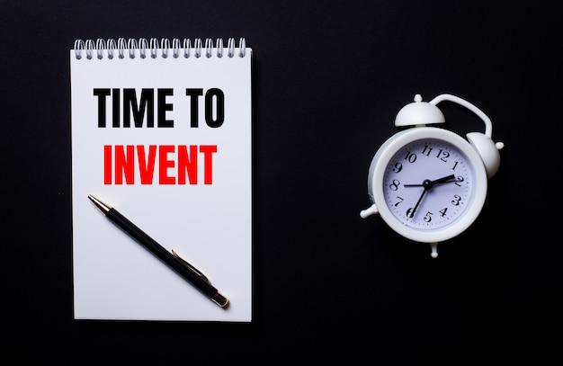 Czas do wynalazku jest zapisany w białym notesie obok białego budzika na czarnej powierzchni
