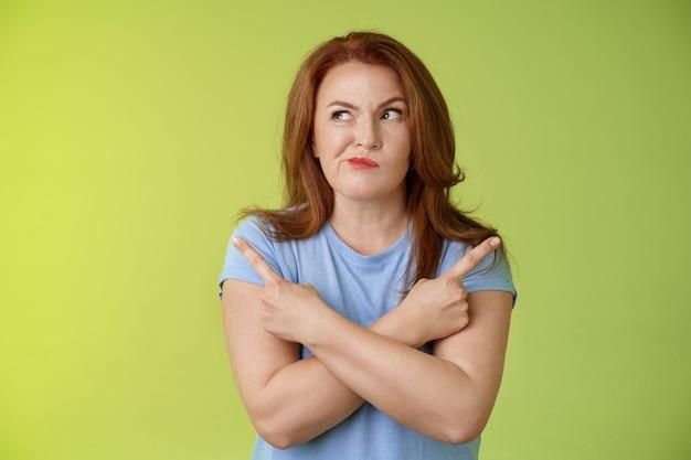 Czas dokonać właściwego wyboru zakłopotana niezdecydowana ruda klientka w średnim wieku decydująca się między kilkoma wariantami skrzyżowane ramiona ciało skierowane w bok spojrzenie w lewo uśmiechnięty niepewnie wątpiący w wybór produktu
