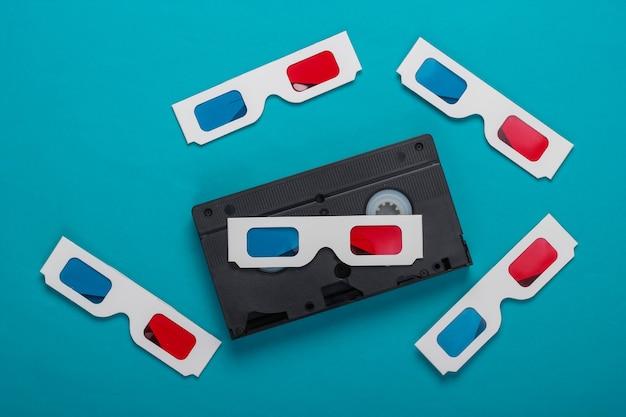 Czas filmu. anaglif jednorazowe papierowe okulary 3d i kaseta wideo na niebieskiej powierzchni. media retro, rozrywka lata 80-te. widok z góry