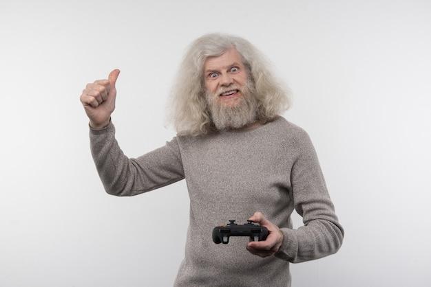 Czas gry. radosny miły człowiek trzymający konsolę do gier podczas grania w gry wideo