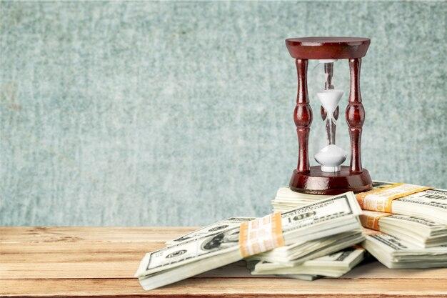 Czas i pieniądze koncepcja obrazu - zegarek piasku i tła pieniędzy.