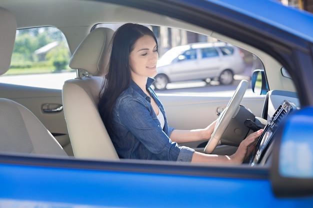 Czas iść. atrakcyjna ładna ładna kobieta trzymając kierownicę i odpalając samochód będąc gotową do wyjazdu