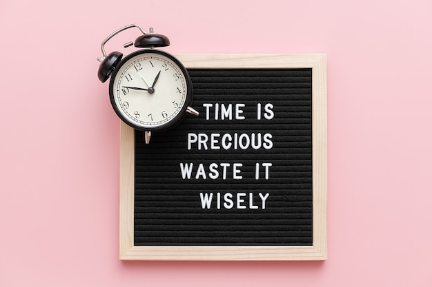 Czas jest cenny, marnuj go mądrze, motywacyjny cytat na kartce i czarny budzik na różowo