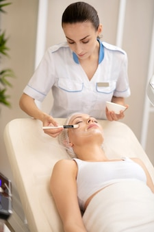 Czas kosmetologa. piękna bizneswoman czuje się zrelaksowana po wizycie w biurze kosmetologa