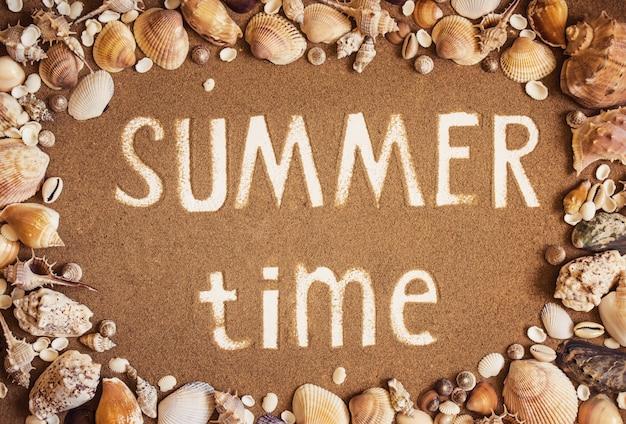 Czas letni jest zapisywany na piasku w ramce muszli morskich.
