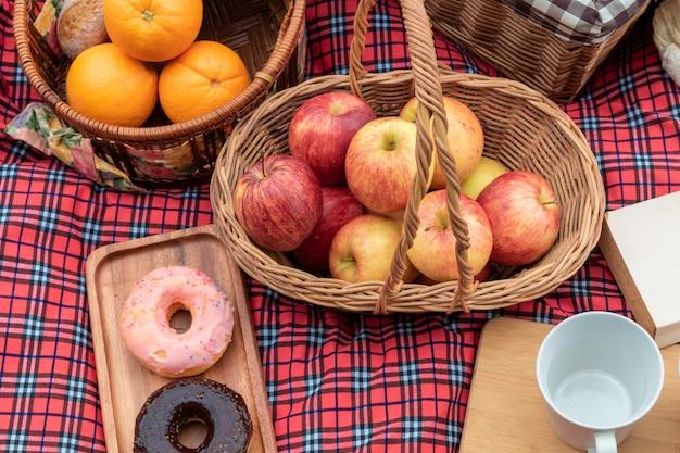 Czas letni zbliżenie koszyka piknikowego z jedzeniem i owocami w przyrodzie.