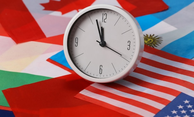 Czas międzynarodowy. biały zegar na tle wielu flag świata