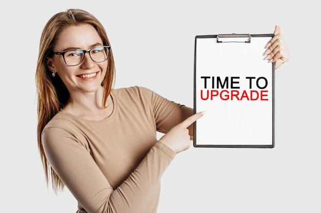 Czas na aktualizację. piękna młoda biznesowa kobieta w okularach trzyma schowek z makietą miejsca na szarym tle