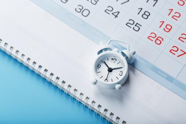 Czas na białym budziku leżącym w kalendarzu i niebieskim tle. widok z góry