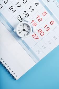 Czas na białym budziku leżącym w kalendarzu i niebieskim tle.
