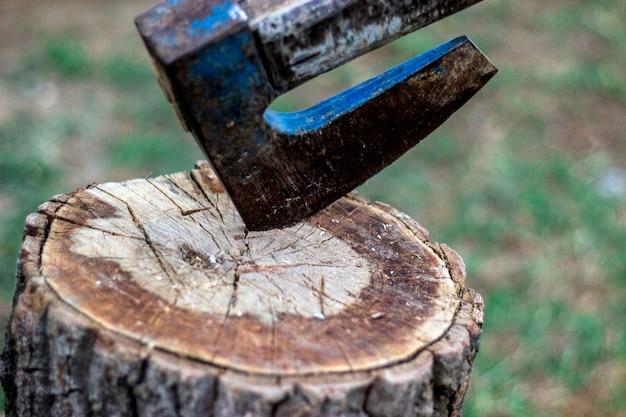Czas na cięcie. stary topór stojący przy usypanych kawałkami drewna opałowego w pniu drzewa