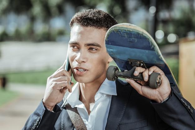 Czas na deskorolce. przyjemny student trzyma deskorolkę i rozmawia przez telefon