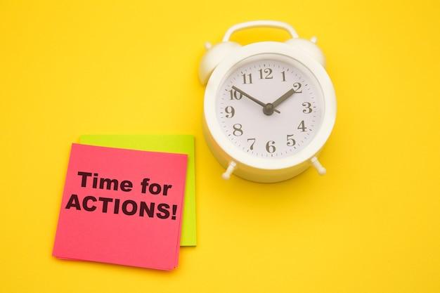 Czas na działanie, tekst na różowej naklejce z białym alarmem na boku.
