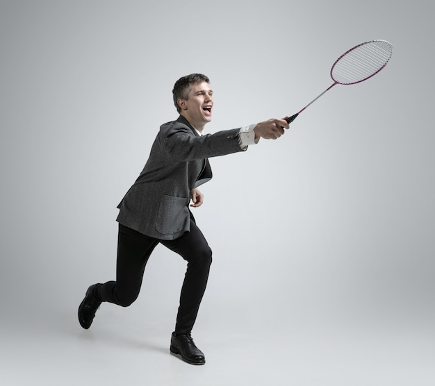 Czas na emocje. mężczyzna w ubraniach biurowych grający w badmintona na szarym tle