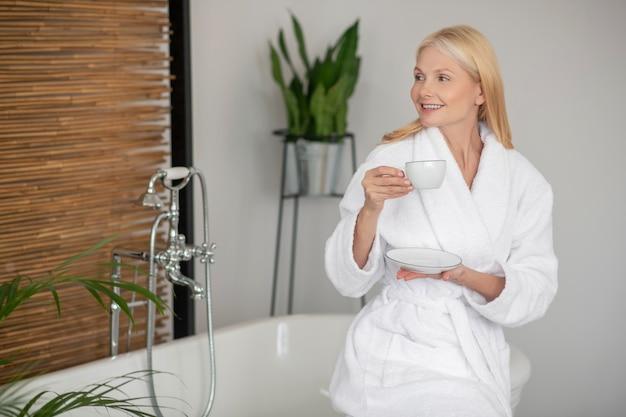 Czas na herbatę. kobieta w białej szacie trzymającej filiżankę z herbatą