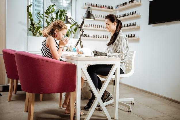 Czas na herbatę. nastoletnia dziewczyna przychodzi do salonu manicure i pije herbatę przed pomalowaniem paznokci