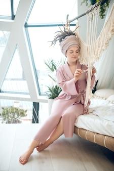 Czas na hobby. młoda kobieta spędza czas w domu zajęta swoją makramą