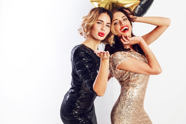 Czas na imprezę dwóch najlepszych przyjaciół w eleganckiej sukni koktajlowej pozowanie. błyszczące złote konfetti. falowana fryzura. balony na przyjęcie.