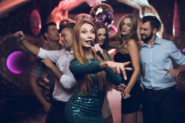 Czas na imprezę. kobieta śpiewa w klubie karaoke