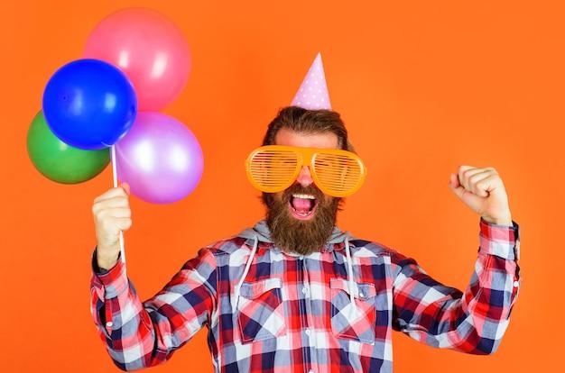 Czas na imprezę. koncepcja radość, zabawa i szczęście. szczęśliwy człowiek z balonami. brodaty mężczyzna w partyjnej czapce i dużych okularach.