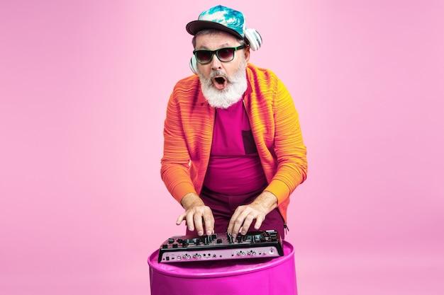 Czas na imprezę. portret starszego hipster człowieka w modne okulary na białym tle na różowym tle studio. koncepcja tech i radosny starszy styl życia. modne kolory, wieczna młodość. miejsce na reklamę.