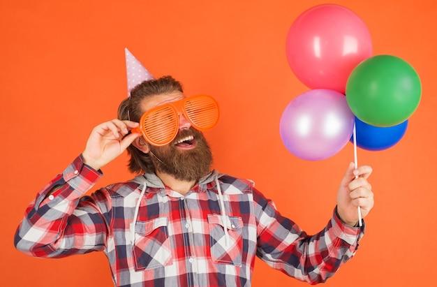 Czas na imprezę. szczęśliwy brodaty mężczyzna z balonami i imprezowymi okularami. święta i uroczystości.