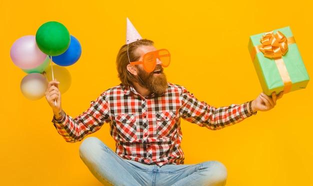 Czas na imprezę. szczęśliwy brodaty mężczyzna z teraźniejszością i balonami. święta i uroczystości.