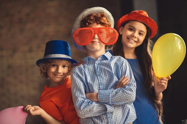 Czas na imprezę. troje dzieci w czapkach pozuje do zdjęcia