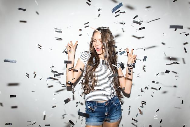 Czas na imprezę. wesoła młoda kobieta wyciągając ręce podczas spadającego na nią konfetti
