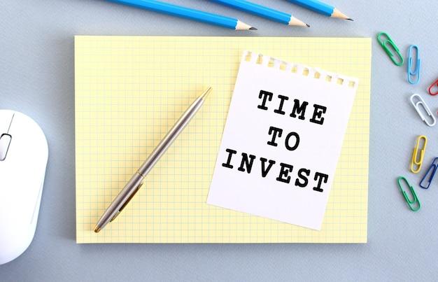 Czas na inwestycje jest zapisany na kartce papieru leżącej na zeszycie obok materiałów biurowych. pomysł na biznes.