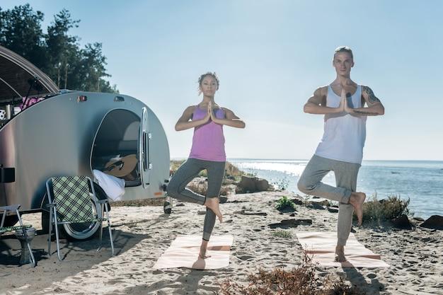 Czas na jogę. para prowadzi zdrowy tryb życia z ulgą, ciesząc się czasem jogi w pobliżu swojej kompaktowej przyczepy