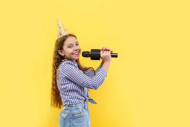 Czas na karaoke, słodka dziewczyna odizolowana na żółtej ścianie, trzymająca mikrofon, dziewczyna w urodzinowej czapce, uśmiechnięta z uśmiechniętą twarzą.