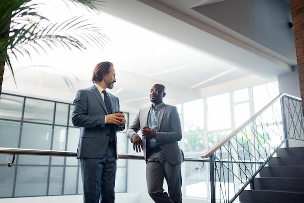 Czas na kawę. brodaty biznesmen rozmawiający z partnerem i mający czas na kawę rano