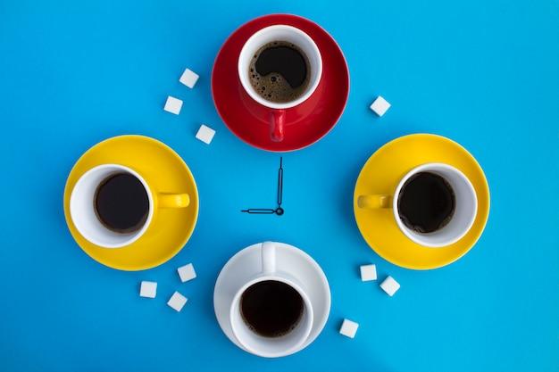 Czas na kawę. kompozycja z czarną kawą w jasnych filiżankach i wskazówkach zegara na środku niebieskiej powierzchni. widok z góry. skopiuj miejsce.