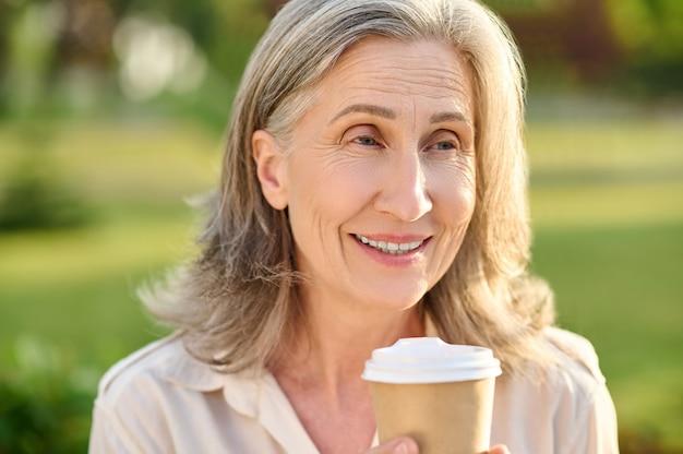 Czas na kawę. optymistyczna uśmiechnięta ładna kobieta w wieku emerytalnym z kawą na zewnątrz w ciepły dzień