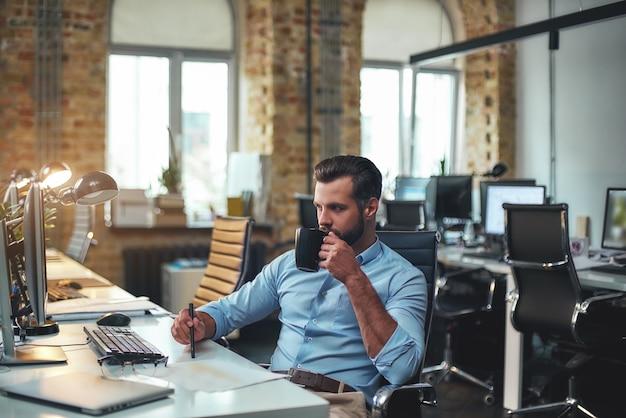 Czas na kawę z boku młodego brodatego biznesmena w wizytowym stroju pracującym na komputerze