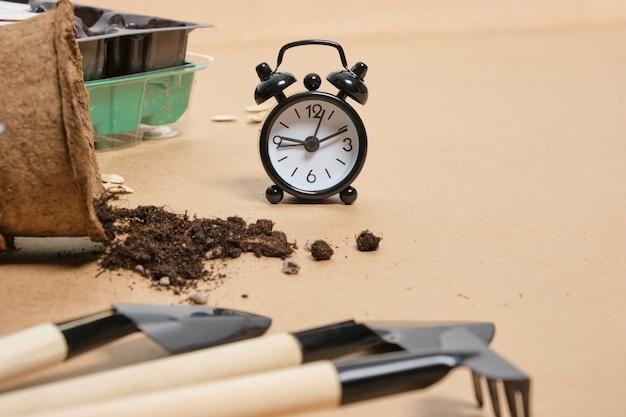 Czas na koncepcję sadzenia sadzonek wiosną, czarny budzik, łopaty i doniczki torfowe do sadzenia nasion na brązowym papierze rzemieślniczym