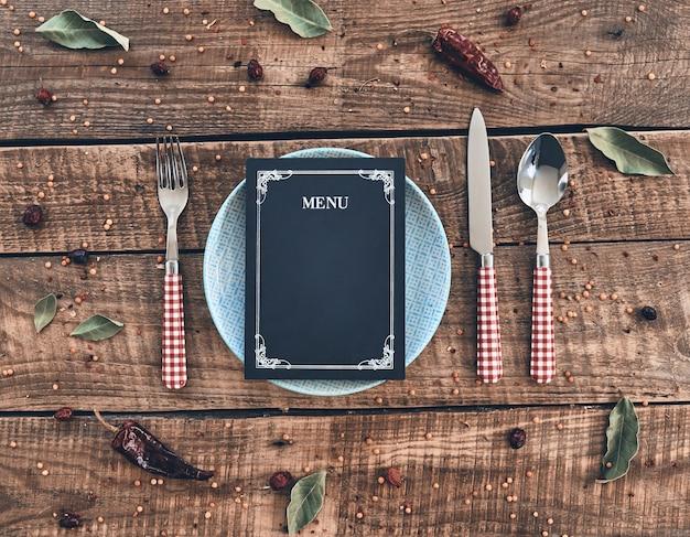 Czas na lunch! ujęcie pod wysokim kątem pustego talerza, widelca, łyżki, noża i zamkniętego menu