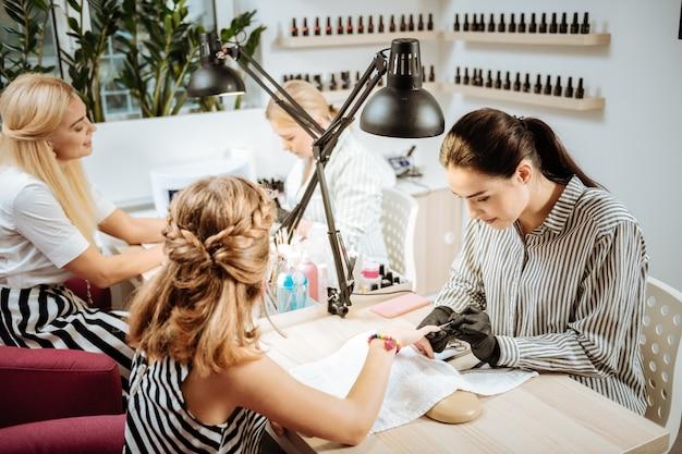 Czas na manicure. stylowa blondyneczka i córka przychodzą do salonu piękności i robią sobie manicure