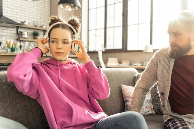 Czas na muzykę. córka słucha muzyki w słuchawkach, nie dzieląc się swoimi problemami z kochającym ojcem
