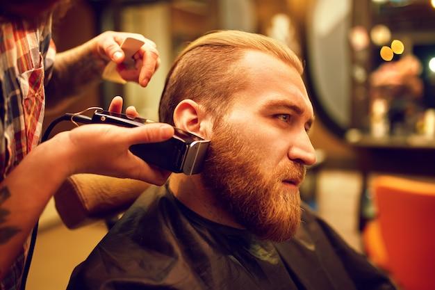 Czas na nową fryzurę. przystojny młody brodaty mężczyzna przyszedł do fryzjera w celu fryzury. styl hipster. koncepcja mody i urody.