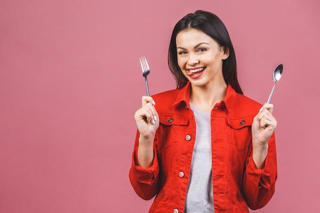 Czas na obiad! portret młodej kobiety piękne na sobie czerwoną koszulę na co dzień, trzymając łyżkę i widelec na białym tle nad różowym tłem.