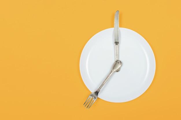 Czas na obiad, talerz jako zegar pokazuje siódmą wieczorem na żółtym tle