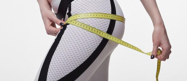 Czas na odchudzanie diety odchudzającej. sprawności fizycznej kobiety napadu dziewczyna w sportswear z miarą taśmy mierzy jej udo na bielu