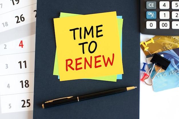 Czas na odnowienie, tekst na żółtym papierze w kształcie kwadratu na niebieskim tle. notatnik, kalkulator, karty kredytowe, długopis, artykuły papiernicze na pulpicie. koncepcja biznesu, finansów i edukacji. selektywne skupienie.