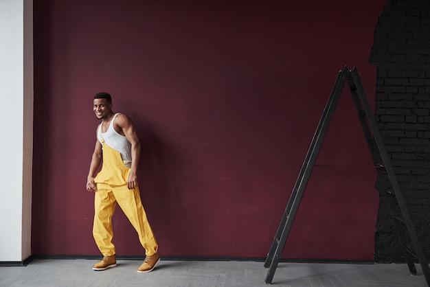Czas na odpoczynek i taniec. młody pracownik afroamerykanin w żółtym mundurze ma jakąś pracę